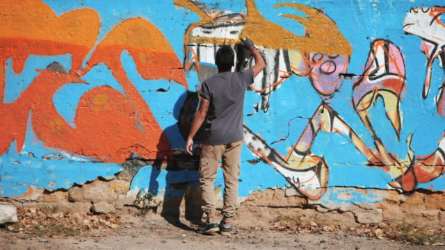 Handsome Talented Young Boy making a colorful graffiti with aerosol spray on urban street wall. Cinematic toned slow motion footage. Creative art. Back view, overall plan video