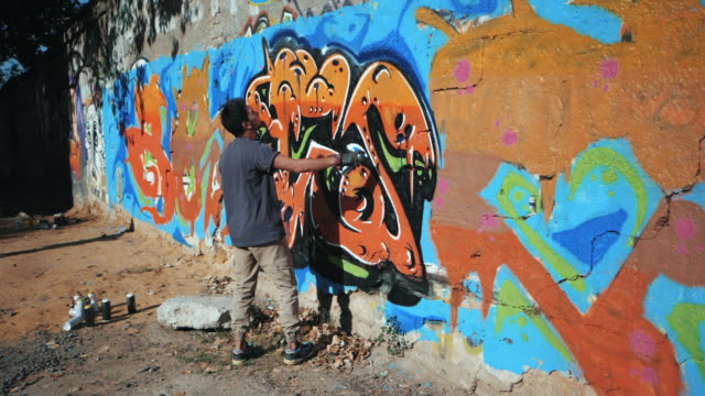 Handsome Talented Young Boy making a colorful graffiti with aerosol spray on urban street wall. Cinematic toned slow motion footage. Creative art. Gimbal shot video