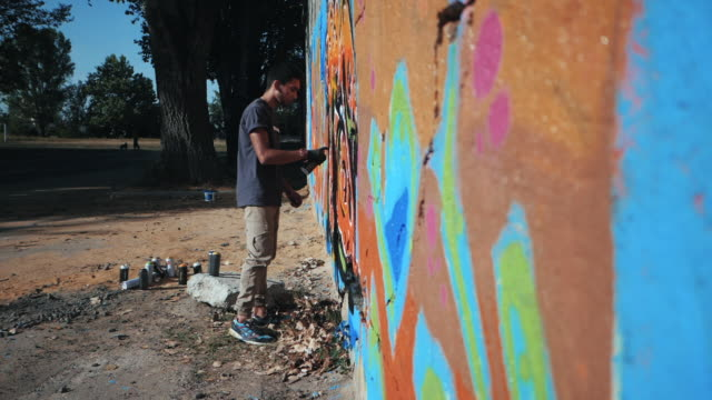 Handsome Talented Young Boy making a colorful graffiti with aerosol spray on urban street wall. Cinematic toned slow motion footage. Creative art. Side view video