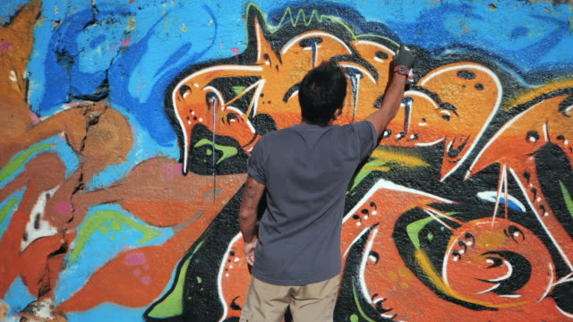 Handsome Talented Young Boy making a colorful graffiti with aerosol spray on urban street wall. Cinematic toned slow motion footage. Creative illegal art. Back view, overall plan video