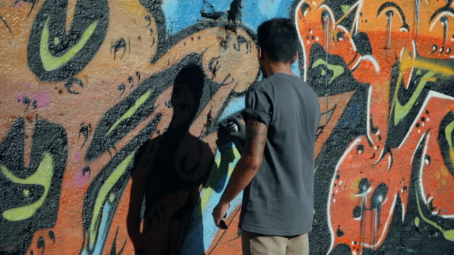 Handsome Talented Young Boy making a colorful graffiti with aerosol spray on urban street wall. Cinematic toned slow motion footage. Creative art video