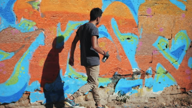Handsome Talented Young Boy walking near his colorful graffiti on urban street wall. Cinematic toned slow motion footage. Creative art video