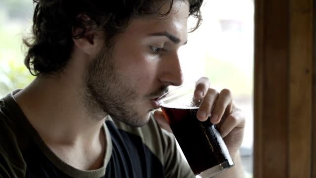 Adolescent beau boire cola assis à la table dans la pub - Vidéo