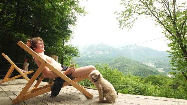 hübscher tourist sitzt auf einer launge - sun chair stock-videos und b-roll-filmmaterial