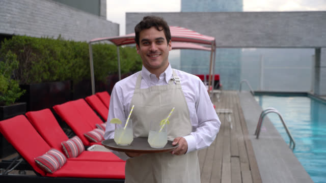 Handsome waiter at the rooftop pool of a luxury hotel holding a tray with drinks smiling at camera Handsome waiter at the rooftop pool of a luxury hotel holding a tray with drinks smiling at camera very happy wait staff stock videos & royalty-free footage