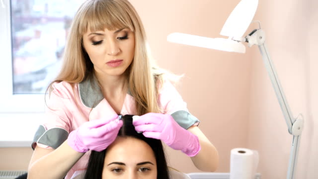 Bидео Handsome woman receives an injection in the head. The concept of mesotherapy. Thrust to strengthen the hair and their growth. Work of the cosmetologist