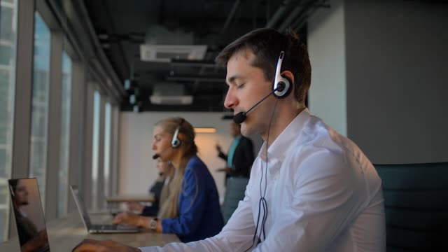 Handsome worker in headset calling to cuctomers in business office call center Handsome worker in headset calling to cuctomers in business office call center. His female colleagues also calling and communicated by phone with clients. cross section stock videos & royalty-free footage