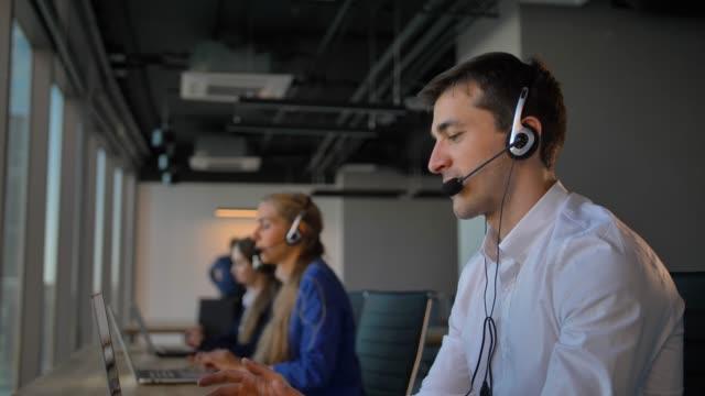 ofis çağrı merkezi müşteri ile konuşurken yakışıklı işçi ve kameraya gülümse - kesit stok videoları ve detay görüntü çekimi