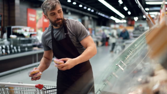 vídeos de stock e filmes b-roll de handsome worker of hypermarket is taking doughnuts from shopping cart and putting them in containers on shelves in bakery department. selling food and people concept. - supermarket worker