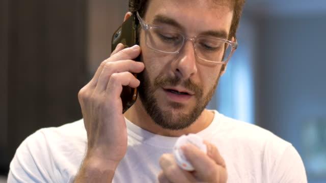 vídeos y material grabado en eventos de stock de guapo joven adulto hombre sosteniendo una botella de píldora y hablando en el teléfono inteligente - receta instrucciones