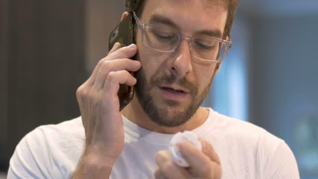 vídeos y material grabado en eventos de stock de atractivo joven adulto sosteniendo una botella de píldora y hablando por teléfono inteligente - receta instrucciones