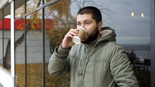 Handsome young bearded man is holding a cup. drinking hot drink coffee or tea in autumn outdoors video