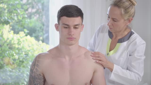 stilig ung brunett man med bruna ögon sitter på soffan i kliniken som läkare kontrollera hans ryggmuskler. porträtt av sportiv tatuerade manliga patienten i akupunktör kontor. healing, medicin. - människorygg bildbanksvideor och videomaterial från bakom kulisserna