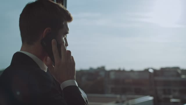 handsome young businessman answering call at work - rispondere video stock e b–roll