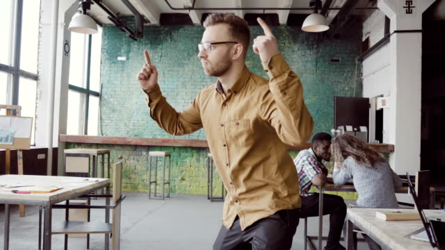 Handsome young businessman doing victory dance about successful achievement. Happy male at modern trendy office video
