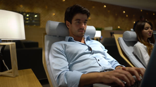 Handsome young businessman relaxing at the airport's VIP lounge working on laptop video