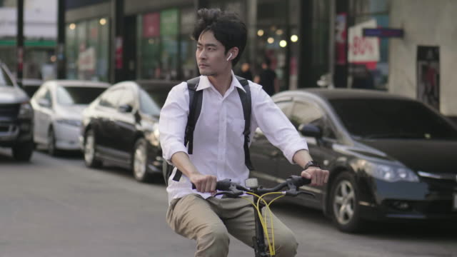 handsome young businessman riding a bicycle in the city