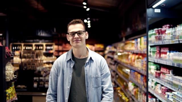 Ein hübscher junger Kaukasier in Brille und blauem Hemd beim Einkaufen im Supermarkt, am Gang vorbei, schaut zu den Seiten und lächelt fröhlich. Zeitlupe – Video