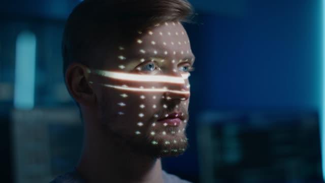 stockvideo's en b-roll-footage met knappe jonge kaukasische man wordt geïdentificeerd door biometrisch gezichtsherkenning scanning proces. futuristisch concept: de projector identificeert individu door gezicht door punten te verlichten en te scannen met laser - medische scan