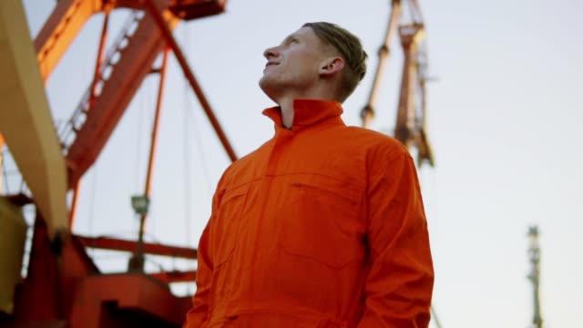 Hübscher Junge Container Lagerarbeiter in orange Uniform durch das Schiff am Hafen stehen und nach oben schauen. Großen Kran im Hintergrund. – Video