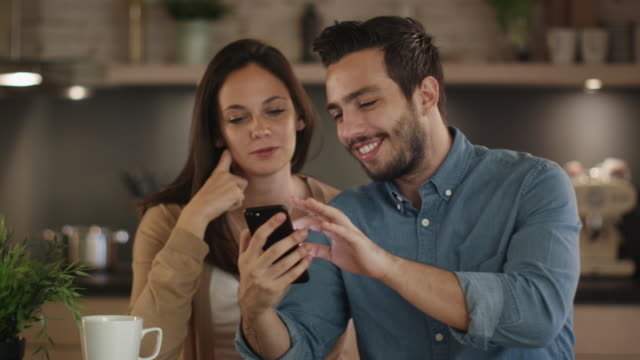 Handsome Young Couple Uses Smartphone while Sitting in the Kitchen.