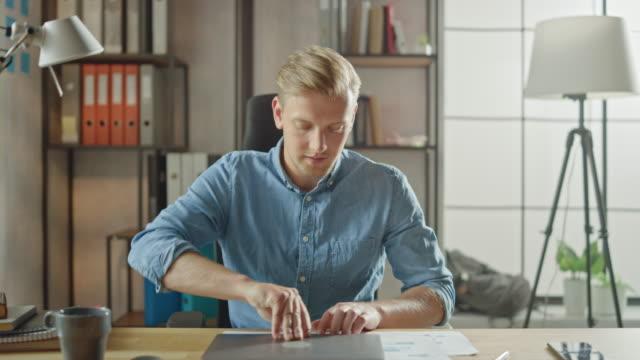 英俊的年輕企業家進入他的辦公室坐在辦公桌上打開筆記本電腦,並開始在專案上工作。商人使用筆記本,寫電子郵件,流覽互聯網,設計創業軟體 - 打開 個影片檔及 b 捲影像