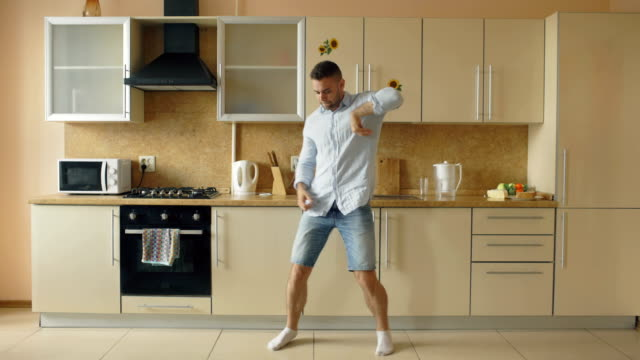 handsome young funny man dancing in kitchen at home in the morning and have fun on holidays - kitchen room video stock e b–roll
