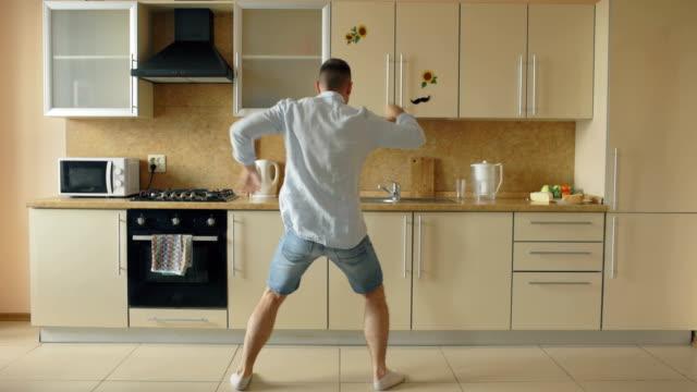 Joven guapo hombre bailando en la cocina en casa en la mañana y divertirse en vacaciones - vídeo
