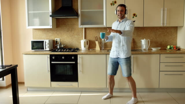 handsome young funny man in headphones dancing and singing in kitchen at home in the morning and have fun on vacation - śpiewać filmów i materiałów b-roll