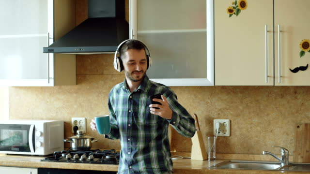 Handsome young funny man in headphones dancing and singing in kitchen at home in the morning and have fun on vacation