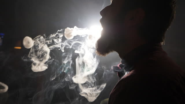 Handsome young guy smoking hookah and makes rings of smoke. Silhouette of handsome young guy smoking hookah and makes rings of smoke at dark room of shisha loudge. The round form of a vapor is flying in the air. Magic arf fog, slow motion. water pipe stock videos & royalty-free footage