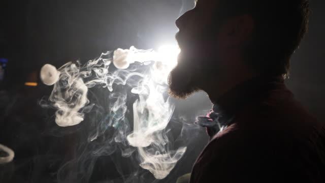 stilig ung kille röka vattenpipa och gör ringar av rök. - water pipes bildbanksvideor och videomaterial från bakom kulisserna