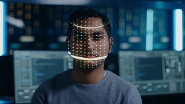 ハンサムな若いインド人は、生体認証顔認識スキャンプロセスによって識別されます。未来的な概念: プロジェクターは、ドットで顔を照らすことによって、個々を識別し、レーザーでスキ� - 医療用スキャン点の映像素材/bロール