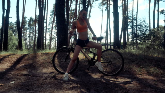 handsome young lady with a Bicycle handsome young lady with a Bicycle in the wood charming stock videos & royalty-free footage