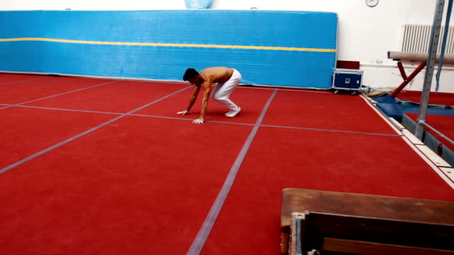 Handsome young male gymnast training on sport mat video