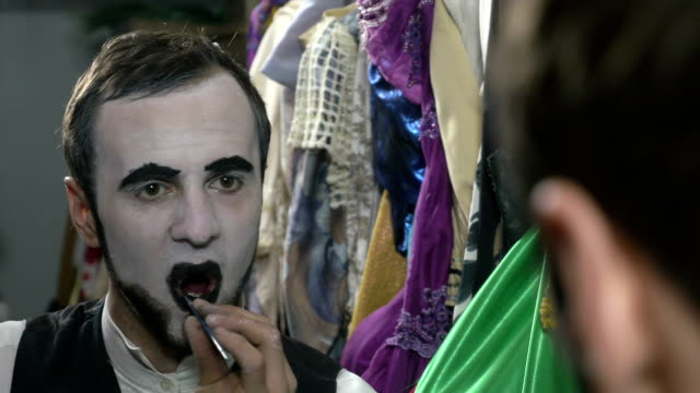 Handsome young man applying black lip stick for mime make-up video