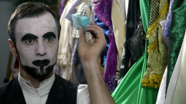 Handsome young man applying white face painting for mime make-up video