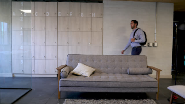 handsome young man arriving to the office walking by the lockers holding his backpack very happy - continente americano video stock e b–roll