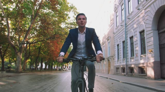 Handsome young man driving his bicycle on the street in park in city center during sunrise, tracking shot, gimbal