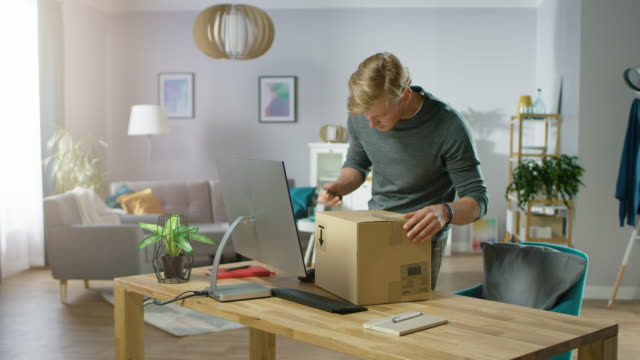 Handsome Young Man Enters His Living Room with Cardboard Box Package, Starts Opening it With Interest.