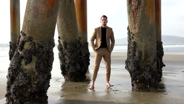 Handsome young man in a suit in the sand at the beach