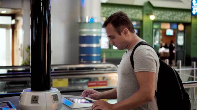 hübscher junger mann im flughafen-terminal. stand in der nähe der ladestation mit touchscreen, surfen - steckschlüssel stock-videos und b-roll-filmmaterial