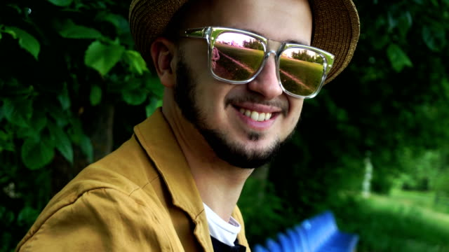 handsome young man in golden mirror sunglasses smiling on camera video