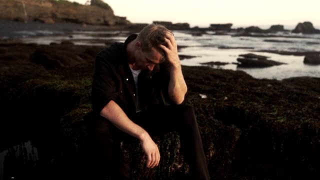 Handsome young man in stylish dark clothes sitting on black beach, enjoying, watching sunset