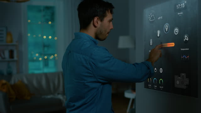 Handsome Young Man Interacts with Augmented Reality Display. He is Turning On the Lights in His Cozy Flat. Young Couple in Smart Home Concept with Transparent Screen Made with VFX Special Effects. video