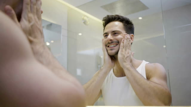 vídeos de stock e filmes b-roll de handsome young man looking at his face and checking his skin in the morning in the bathroom - espelho