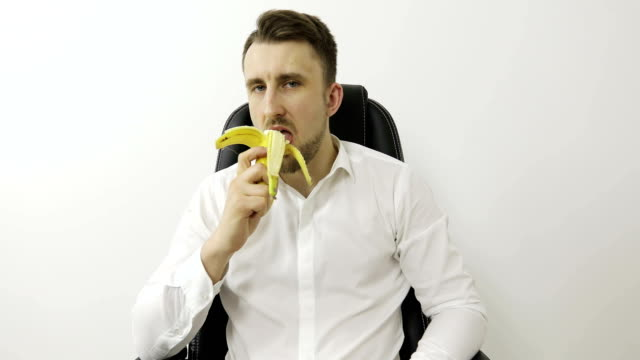 A handsome young man looks at the camera and eats a fresh banana. video