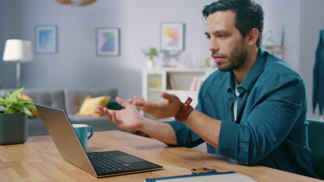 hübscher junger mann macht videoanruf mit seinem laptopcomputer. seiner sitzung am schalter im gemütlichen wohnzimmer. - webinar stock-videos und b-roll-filmmaterial