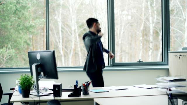 ハンサムな若い男オフィス ワーカーは、オフィスでのダンスは、自由と良いムードを楽しむジャケットを脱いでします。企業の楽しさ、ひげを生やした男と青年の概念。 ビデオ