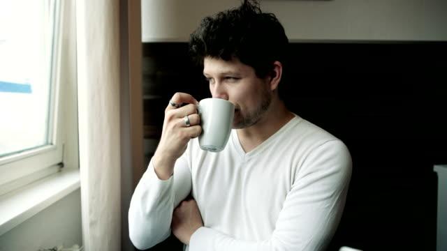 handsome young man on kitchen with cup in hands. - djurarm bildbanksvideor och videomaterial från bakom kulisserna